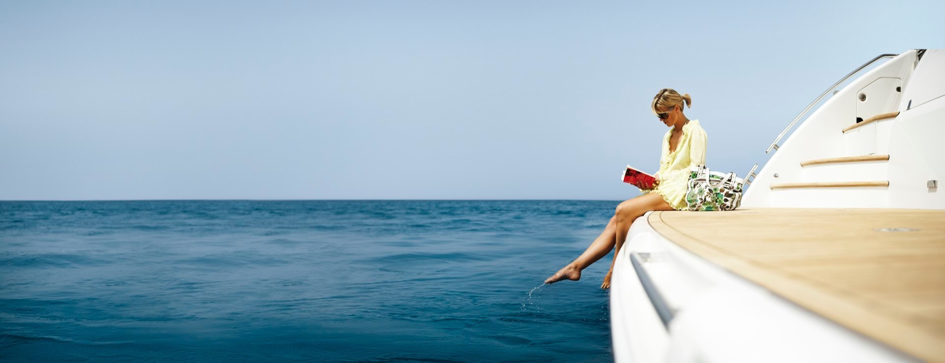 A yachting wallpaper photo of a girl on the aft deck on a luxury yacht.